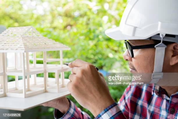 an asian architect looking at building model out office. - 建築模型 ストックフォトと画像