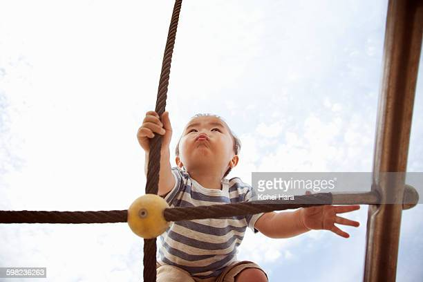 an asian baby boy walking tightropes