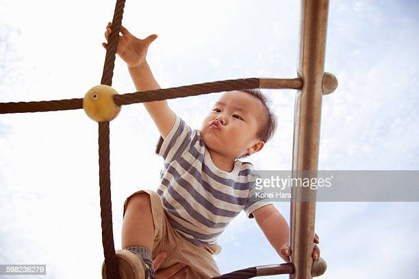 an asian baby boy walking tightropes - ジャングルジム ストックフォトと画像