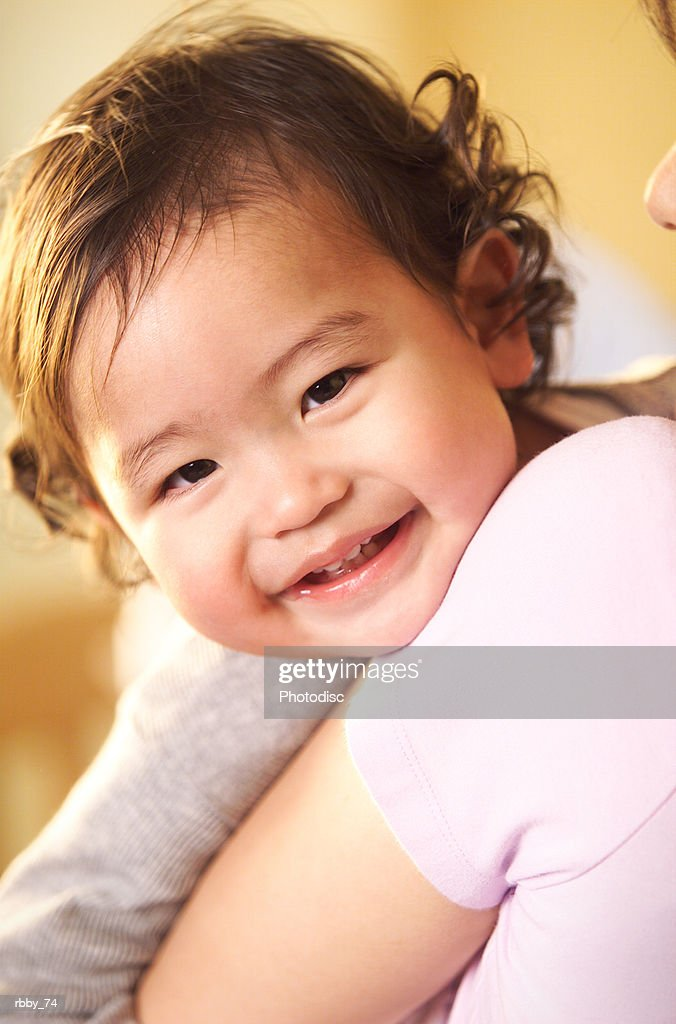 an asian baby smiles brightly while being held by his mother : Stockfoto
