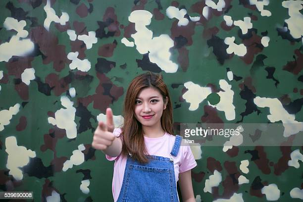 An Asian Beauty Young Woman Standing in Front of Camouflage Wall with Gun Finger Gesture