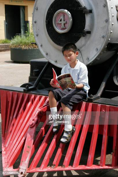 An Asian boy sat on the front of a train reading a book at the Huntsville Depot Museum