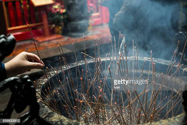 An Asian Buddhist Worshiper Lighting a Stick for Praying in Front of Burning Incense Burner, Censer with Inclined, Oblique Light
