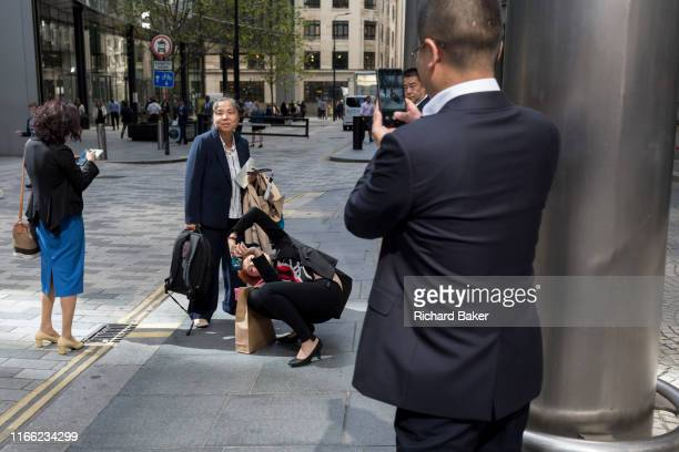 An Asian business lady visitor comically contorts her body in order to take a photo of a colleague against London skyscrapers in the City of London...