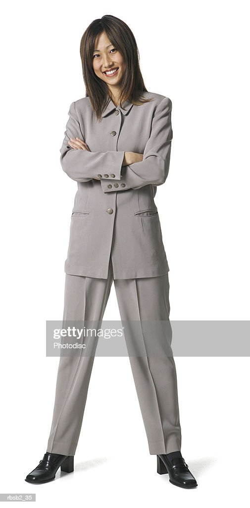 an asian business woman in a grey pant suit folds her arms and smiles : Foto de stock