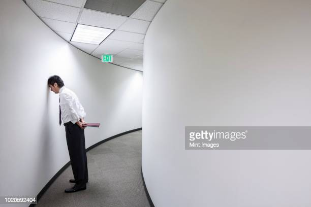an asian businessman frustrated and standing with his head against a wall in a hallway. - fracasso imagens e fotografias de stock