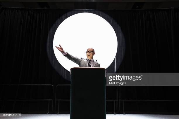 an asian businessman standing at a podium giving a talk at a convention. - persuasion stock pictures, royalty-free photos & images