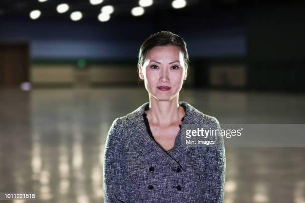 An Asian businesswoman  standing in a dimly lit and dark exhibition area in a convention centre.