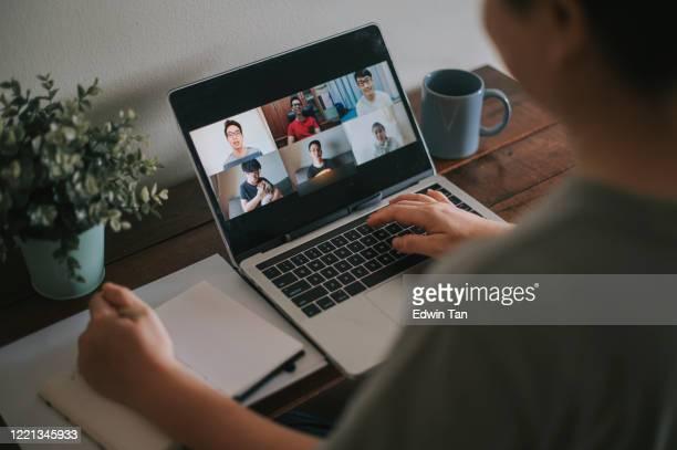 une femme adulte mi-adulte chhinese asiatique à la conférence vidéo de home office avec des vêtements occasionnels utilisant l'ordinateur portatif - messagerie en ligne photos et images de collection