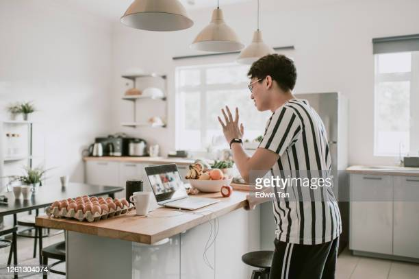 an asian chhinese young adult man at home kitchen counter video conference with his friends casual clothing using laptop - new normal concept stock pictures, royalty-free photos & images