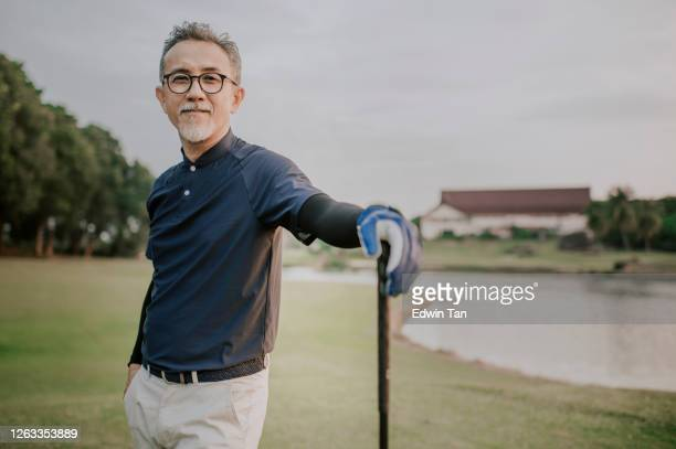 an asian chinese active senior man golfer standing with his golf club driver in the golf course after the golf game waiting and looking - golfer stock pictures, royalty-free photos & images