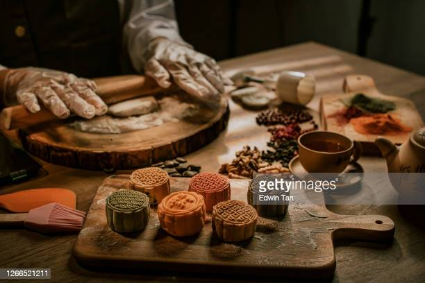an asian chinese beautiful woman making chinese traditional mid-autumn snow skin mooncake at her kitchen - moon cake stock pictures, royalty-free photos & images
