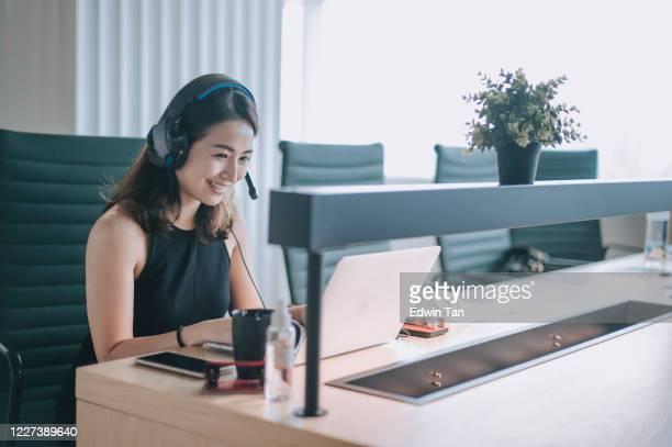 een aziatische chinese mooie vrouwen witte boordenarbeider die aan de video die videoconferentie van de camera roept met zijn bedrijfspartners met gezichtsmasker spreekt - zuidoost aziatische etniciteit stockfoto's en -beelden