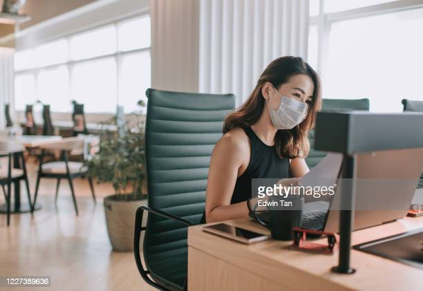 an asian chinese beautiful woman white collar worker working in coworking office with face mask on for illness prevention - new normal stock pictures, royalty-free photos & images