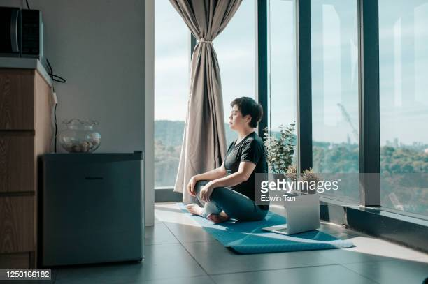 an asian chinese beautiful woman workout at home mediating on yoga mat at kitchen corner near the window on weekend morning - mediation stock pictures, royalty-free photos & images