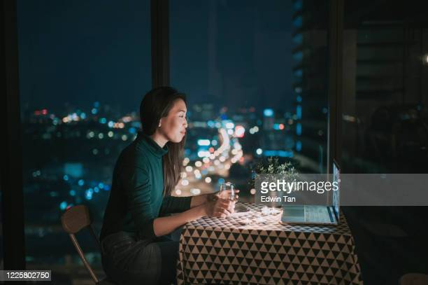 an asian chinese beautiful young lady having dessert in her apartment during magic hour, dusk and talking to her boyfriend thru internet using her laptop - online dating stock pictures, royalty-free photos & images