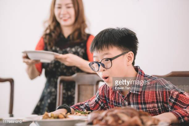 an asian chinese boy feeling excited on his chinese new year's eve reunion dinner prepared and served by his mother - malaysian culture stock pictures, royalty-free photos & images