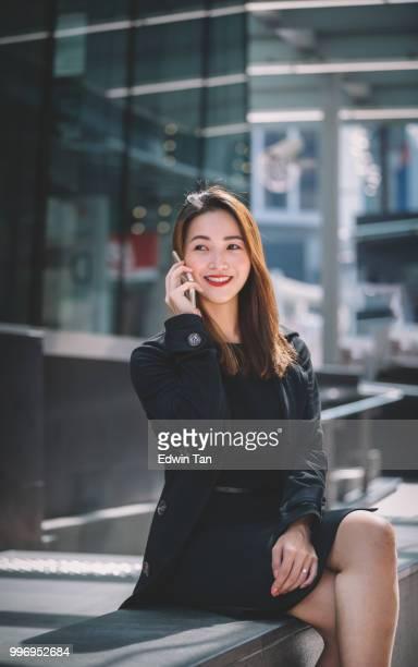 une femme d'affaires chinoise asiatique assis sur le bord de la route parle au téléphone