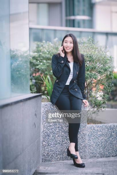 une femme d'affaires chinoise asiatique parlant au téléphone sur le côté de la route