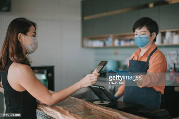 an asian chinese cafe owner businesswoman receiving payment from her customer at counter using qr code contactless payment - new normal stock pictures, royalty-free photos & images