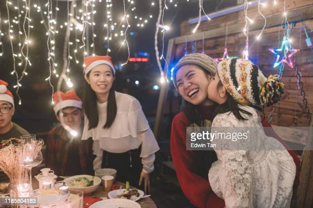 an asian chinese child kissing her elder sister during a christmas party dinner garthering