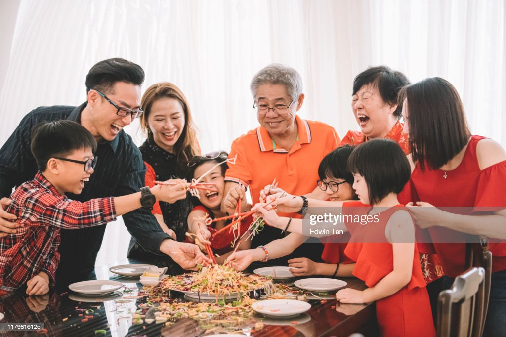 an asian chinese family celebrating chinese new year's eve with traditional food Lou sang (raw fish dishes) during reunion dinner : Stock Photo