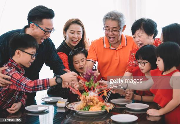 an asian chinese family celebrating chinese new year's eve with traditional food lou sang (raw fish dishes) during reunion dinner - chinese new year stock pictures, royalty-free photos & images
