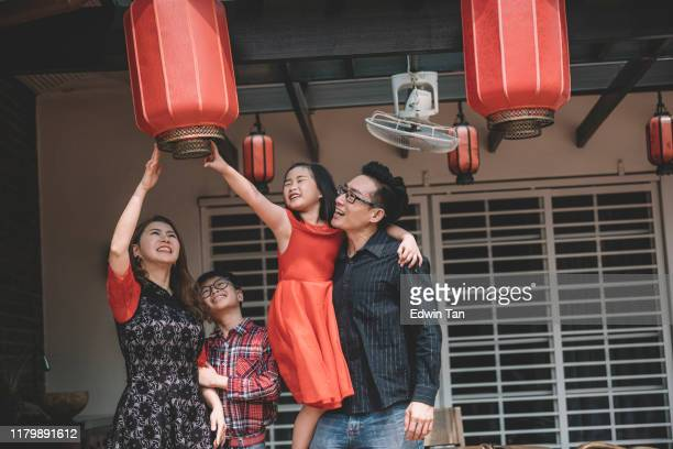 an asian chinese family in malaysia fixing their red lanterns for chinese new year preparation in front of their house - chinese new year stock pictures, royalty-free photos & images