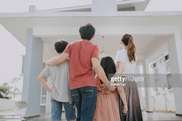 une famille chinoise asiatique se déplaçant dans la nouvelle maison admirant leur maison - maison photos et images de collection