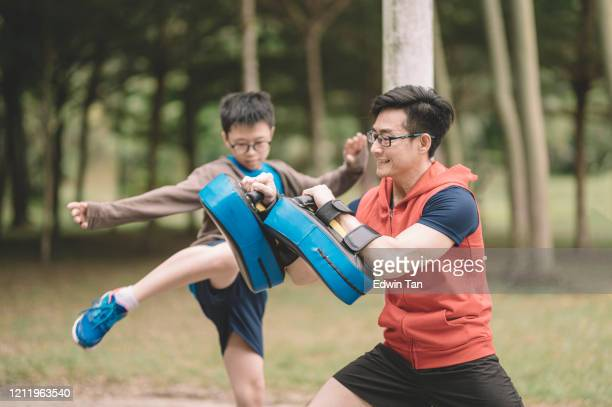 een aziatische chinese vaderatleet die zijn 12 jaarzoon in het openbare park in het avond kickboksen optraint - vechtkunst stockfoto's en -beelden