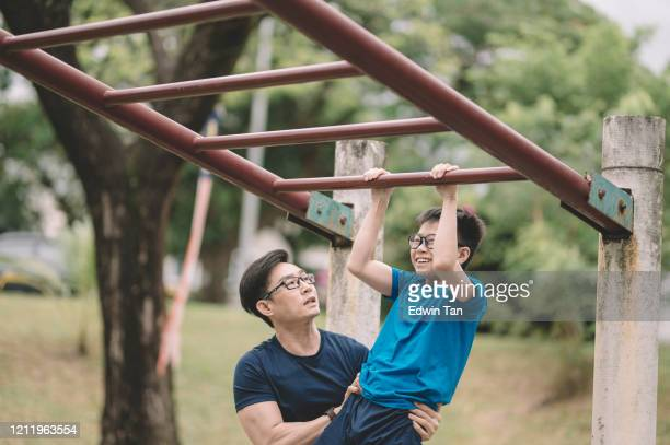 an asian chinese father athlete training his 12 years son in the public park in the evening lift up bar - 12 13 years stock pictures, royalty-free photos & images