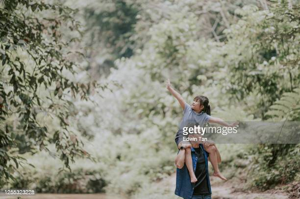 an asian chinese father carrying his daughter on shoulder in the jungle enjoying bonding time together at the river during weekend leisure time - beauty in nature stock pictures, royalty-free photos & images