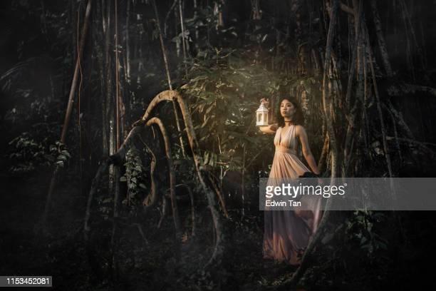 ein asianisches chinesisches weibchen im dschungel in der nacht hält eine lampe aus - rätsel stock-fotos und bilder