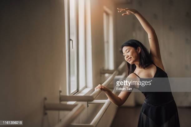 an asian chinese female ballet dancer practising in ballet studio near window waist up - ballet stock pictures, royalty-free photos & images