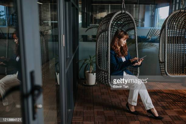 an asian chinese female businesswoman sitting on a rattan hanging chair with her digital tablet in lounge - chairperson stock pictures, royalty-free photos & images