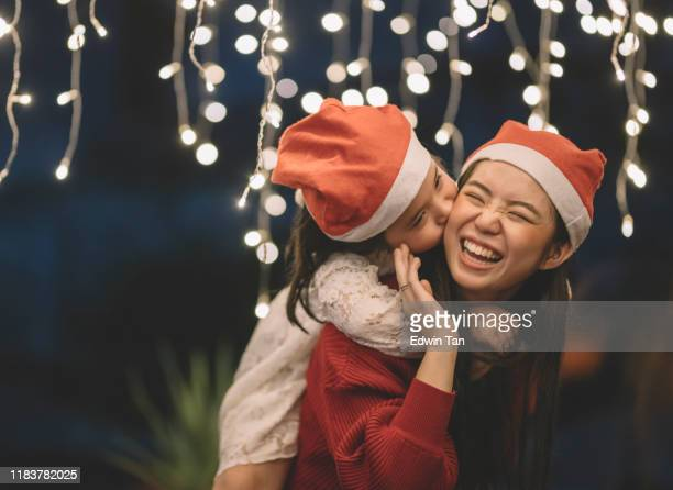 an asian chinese female carrying her sister from the back during christmas eve dinner celebration - christmas family stock pictures, royalty-free photos & images