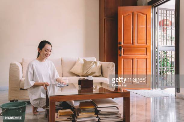 an asian chinese female cleaning her house wiping the table during weekend - daily bucket stock pictures, royalty-free photos & images