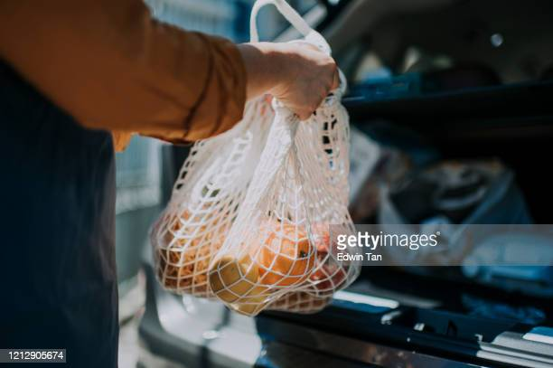 an asian chinese  female delivery person getting the groceries and fruit her customer order online shopping in recycle bags from her car trunk and deliver it to her customer - packaging stock pictures, royalty-free photos & images