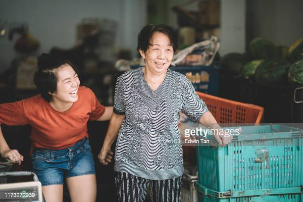 an asian chinese female fruit store retail senior owner and her granddaughter at her store