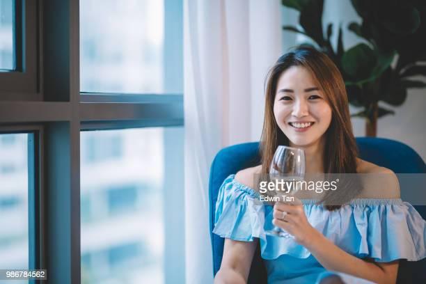 une femme d'origine asiatique chinoise tenant un verre de vin en regardant la caméra