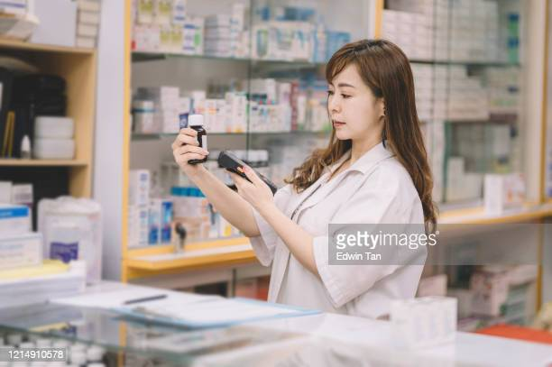 an asian chinese female pharmacist scanning on a bottle of pills for the pricing details at the cashier counter - labeling stock pictures, royalty-free photos & images