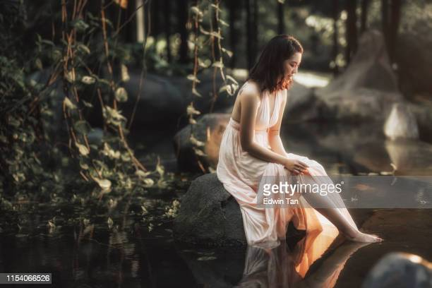 an asian chinese female portrait in the forest with morning sunlight at the pool of water - princess stock pictures, royalty-free photos & images
