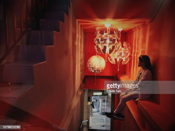 an asian chinese female sitting at the staircase looking at the lamp light