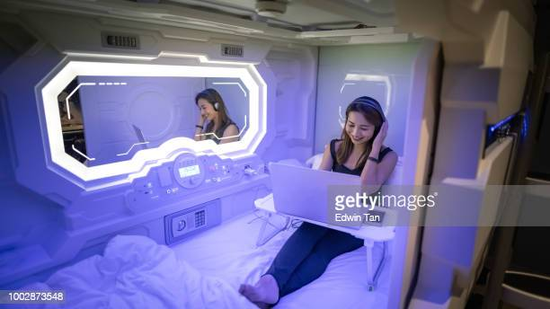 an asian chinese female staying in a capsule hotel room listening to music with her headset while surfing the internet thru her laptop