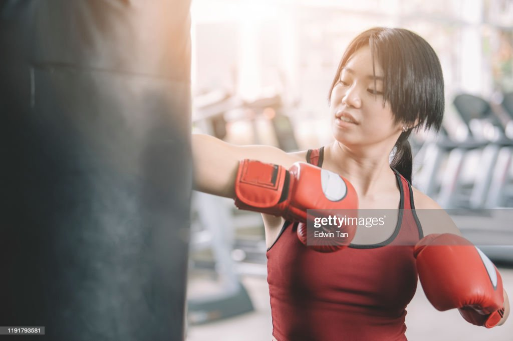 an asian chinese female teenager athlete wearing boxing gloves workout in gym during weekend : Stock Photo