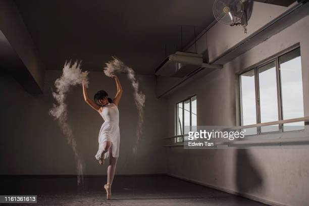 an asian chinese female teenager ballet dancer practising in ballet studio during day time dancing with powder