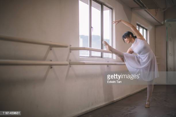 an asian chinese female teenager ballet dancer practising in ballet studio during day time