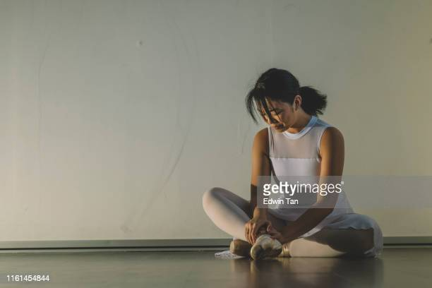 an asian chinese female teenager hurt her leg during practise in her ballet studio and sit on the floor with pain - asian women feet stock pictures, royalty-free photos & images