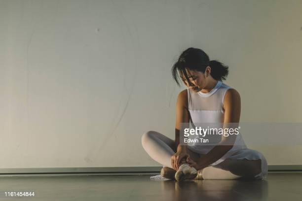 um adolescente chinês asiático fêmea machucou seu pé durante a prática em seu estúdio de balé e sentar-se no chão com dor - bailarina - fotografias e filmes do acervo