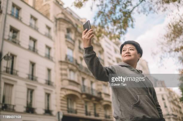un voyageur chinois asiatique prenant selfie dans la rue de la ville de paris - shooting photo photos et images de collection